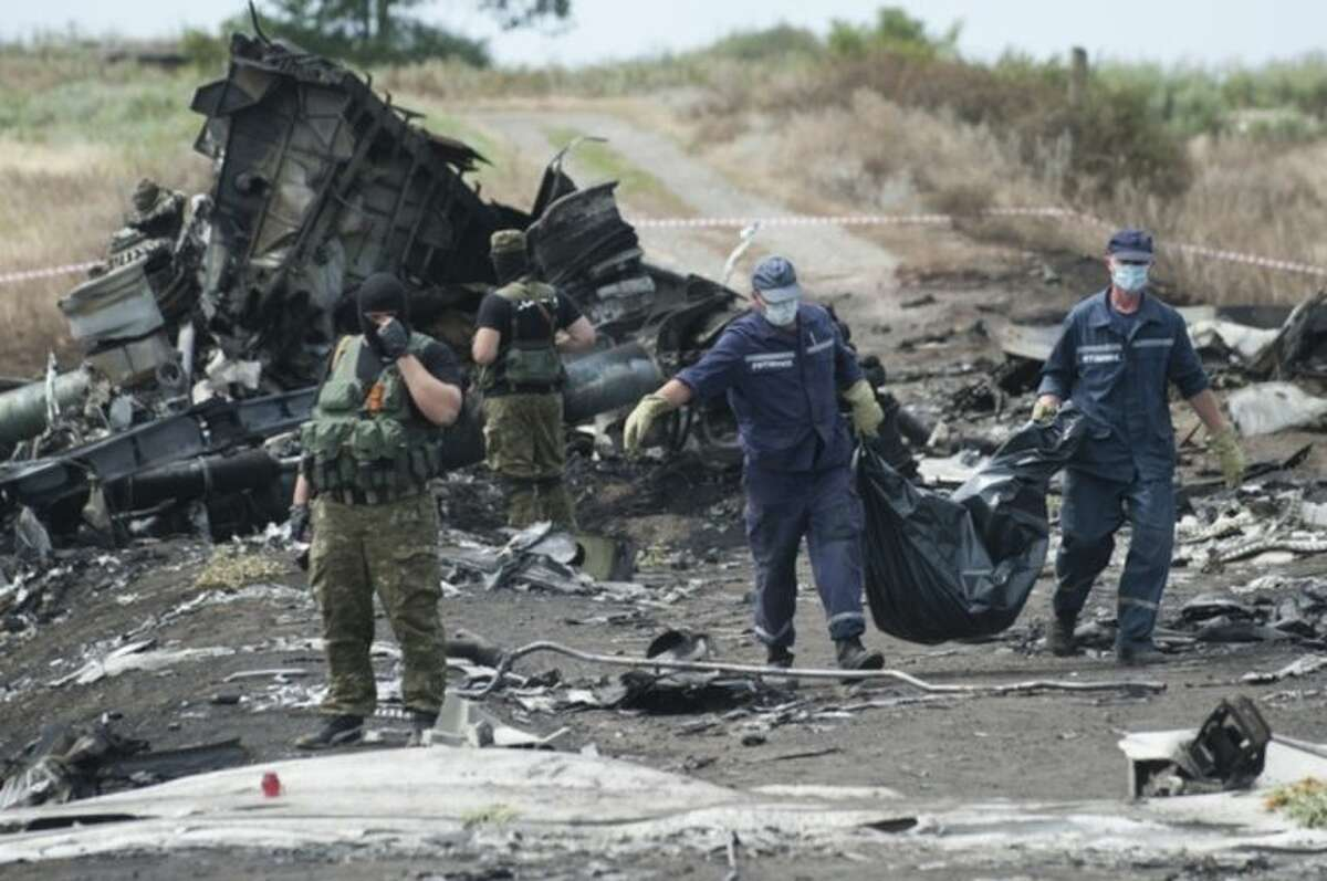 Ukrainian Emergency workers carry a stretcher with a victim's body in a bag as pro-Russian fighters stand in guard at the crash site of Malaysia Airlines Flight 17 near the village of Hrabove, eastern Ukraine, Sunday, July 20, 2014. Rebels in eastern Ukraine took control Sunday of the bodies recovered from downed Malaysia Airlines Flight 17, and the U.S. and European leaders demanded that Russian President Vladimir Putin make sure rebels give international investigators full access to the crash site. (AP Photo/Evgeniy Maloletka)