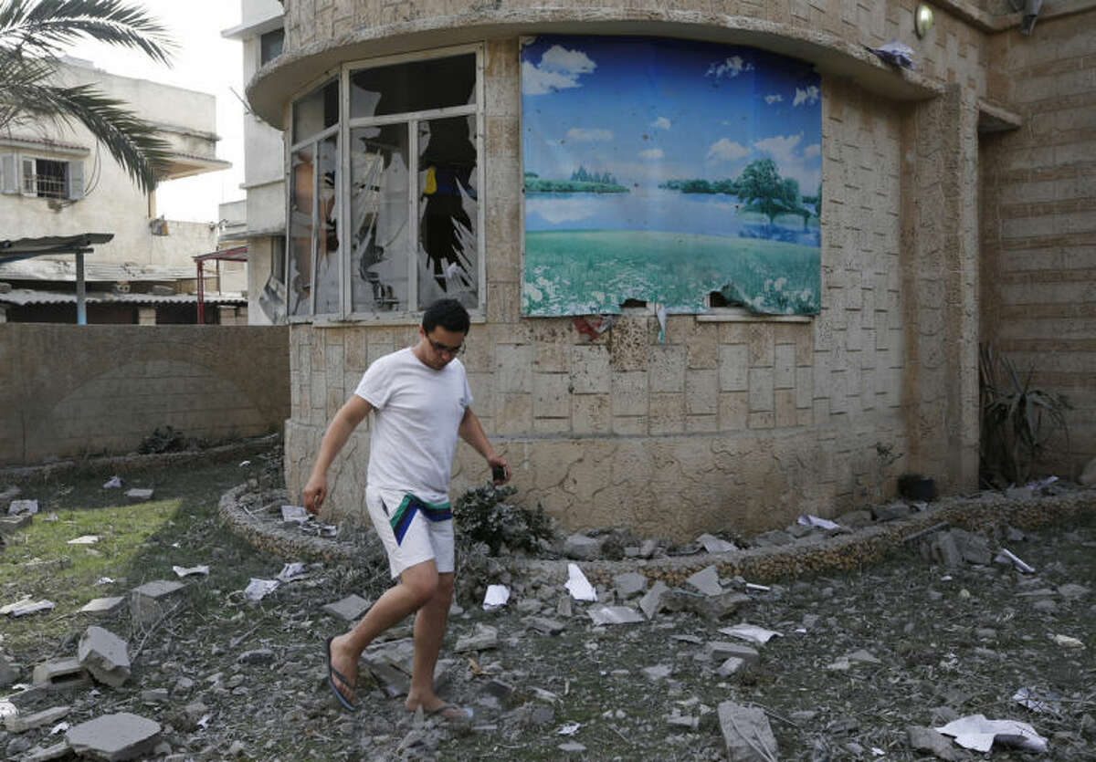 A man walks on debris from his damaged house, hit by an overnight Israeli strike, in Gaza City, Monday, July 21, 2014. On Sunday, the first major ground battle in nearly two weeks of Israel-Hamas fighting exacted a steep price, killing scores Palestinians and over a dozen Israeli soldiers and forcing thousands of terrified Palestinian civilians to flee their devastated Shijaiyah neighborhood, which Israel says is a major source for rocket fire against its civilians. (AP Photo/Lefteris Pitarakis)