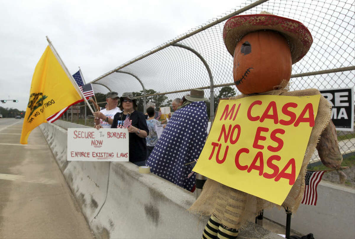 Protesters line the overpass during a protest against people who immigrate illegally, Saturday, July 19, 2014, in Conroe, Texas. Texas Gov. Rick Perry took his border security criticisms to an audience of Hispanic ministers in San Antonio, telling them the federal government should put more Border Patrol troops on the ground and drones in the air to secure the Texas-Mexico border. (AP Photo/Conroe Courier, Jason Fochtman)