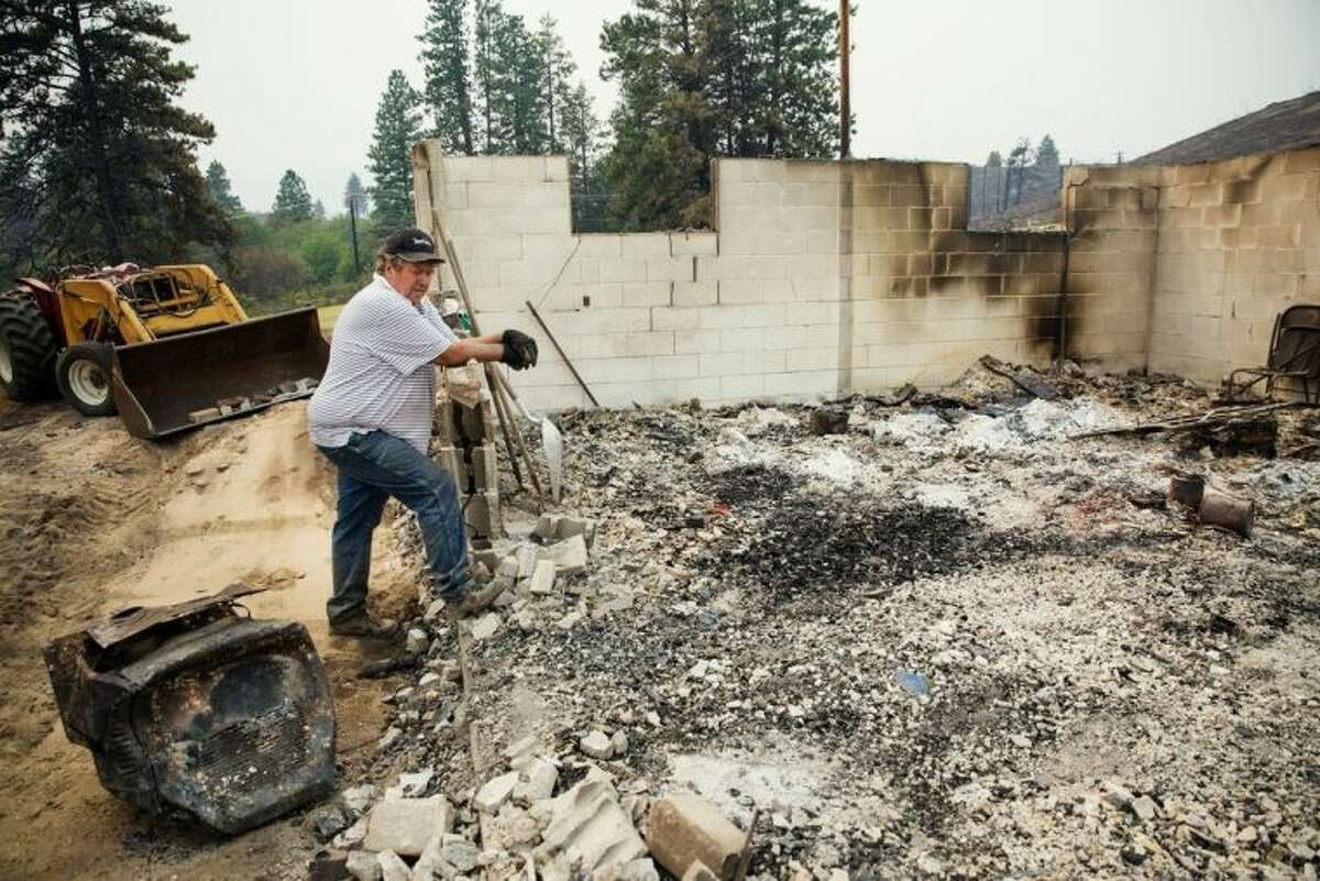 John Johnson returns to clear out and salvage remnants of his burned down home on Chiliwist Road, after the Carlton Complex fire burned through the valley, near Malott, Wash., on Sunday, July 20, 2014. (AP Photo/The Seattle Times, Marcus Yam) SEATTLE OUT; USA TODAY OUT; MAGS OUT; TELEVISION OUT; NO SALES; MANDATORY CREDIT TO BOTH THE SEATTLE TIMES AND THE PHOTOGRAPHER
