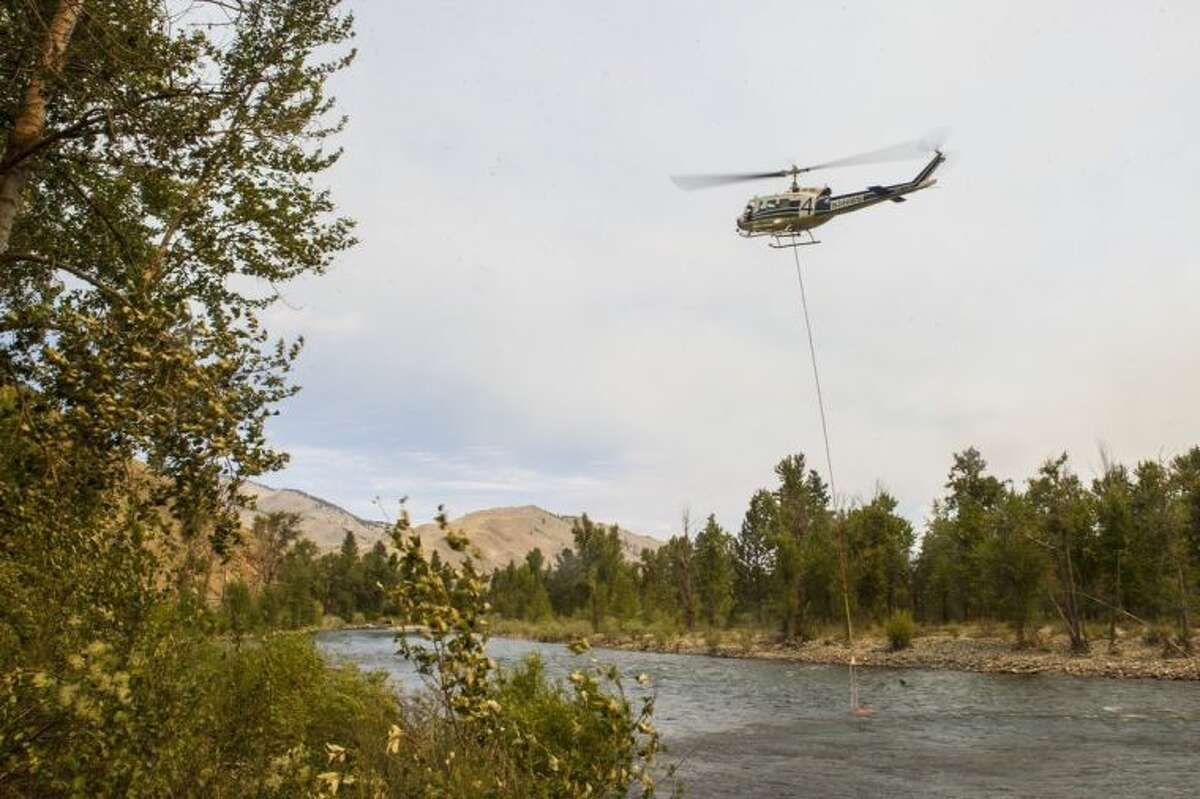 A helicopter refills with water in the Methow River onSunday, July 20, 2014, in Carlton, Washington. The Carlton Complex fires have swept the region covering over 215,000 acres of land and destroying over 100 structures. Fire crews have been called in from all over the country in order to help contain the fire. (AP Photo/The Seattle Times, Maddie Meyer) SEATTLE OUT; USA TODAY OUT; MAGS OUT; TELEVISION OUT; NO SALES; MANDATORY CREDIT TO BOTH THE SEATTLE TIMES AND THE PHOTOGRAPHER