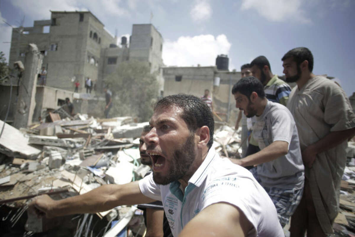 A Palestinian overcome by emotion watches rescuers carry a body from the rubble of a house which was destroyed by an Israeli missile strike, in Gaza City, Monday, July 21, 2014. On Sunday, the first major ground battle in two weeks of Israel-Hamas fighting exacted a steep price, killing scores Palestinians and over a dozen Israeli soldiers and forcing thousands of terrified Palestinian civilians to flee their devastated Shijaiyah neighborhood, which Israel says is a major source for rocket fire against its civilians. (AP Photo/Khalil Hamra)