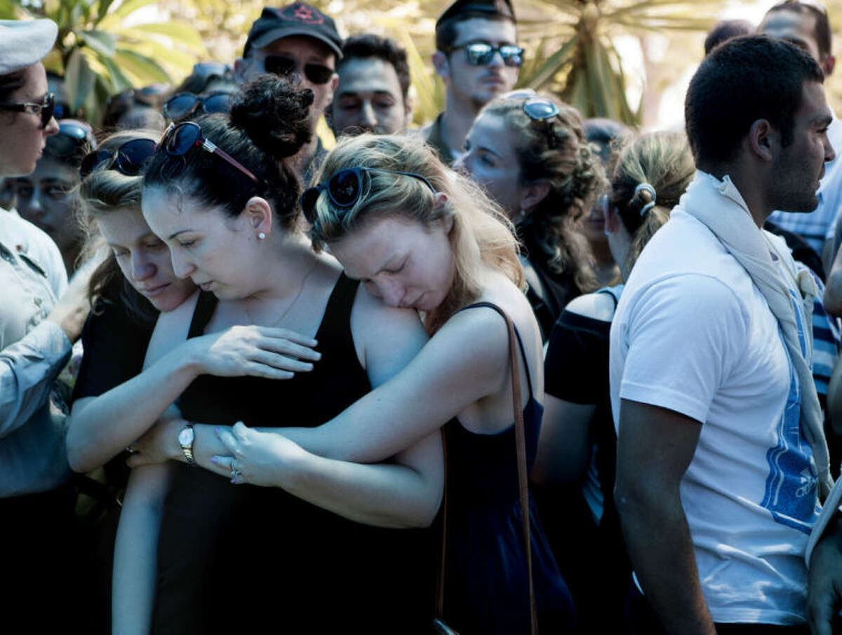 Family and friends of Maj. Tzafrir Bar-Or, 32, one of 13 solider's who were killed in several separate incidents in Shijaiya on Sunday, mourn during his funeral at the military cemetery in Holon, Monday, July 21, 2014. On Sunday, the first major ground battle in two weeks of Israel-Hamas fighting exacted a steep price, killing scores of Palestinians and more than a dozen Israeli soldiers and forcing thousands of terrified Palestinian civilians to flee their devastated Shijaiyah neighborhood, which Israel says is a major source for rocket fire against its civilians. The 13 Israeli soldiers were killed in Shijaiya, in gun battles and rocket attacks. In the deadliest, Gaza fighters detonated a bomb near an armored personnel carrier, killing seven soldiers inside, the army said. In another incident, three soldiers were killed when they became trapped in a burning building, it said. (AP Photo/Dan Balilty)