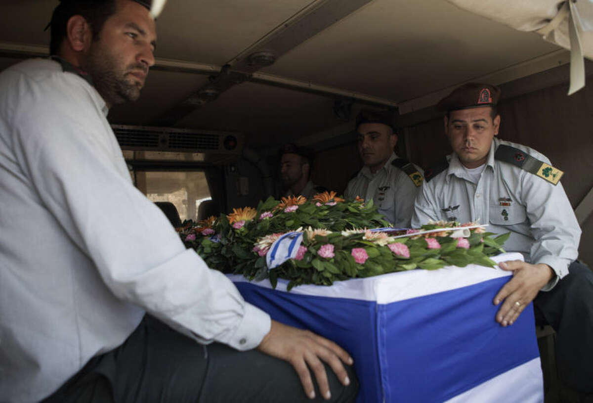 Israeli soldiers escort the coffin of Maj. Tzafrir Bar-Or, 32, one of 13 solider's who were killed in several separate incidents in Shijaiya on Sunday, during his funeral at the military cemetery in Holon, Monday, July 21, 2014. On Sunday, the first major ground battle in two weeks of Israel-Hamas fighting exacted a steep price, killing scores of Palestinians and more than a dozen Israeli soldiers and forcing thousands of terrified Palestinian civilians to flee their devastated Shijaiyah neighborhood, which Israel says is a major source for rocket fire against its civilians. The 13 Israeli soldiers were killed in Shijaiya, in gun battles and rocket attacks. In the deadliest, Gaza fighters detonated a bomb near an armored personnel carrier, killing seven soldiers inside, the army said. In another incident, three soldiers were killed when they became trapped in a burning building, it said. (AP Photo/Dan Balilty)
