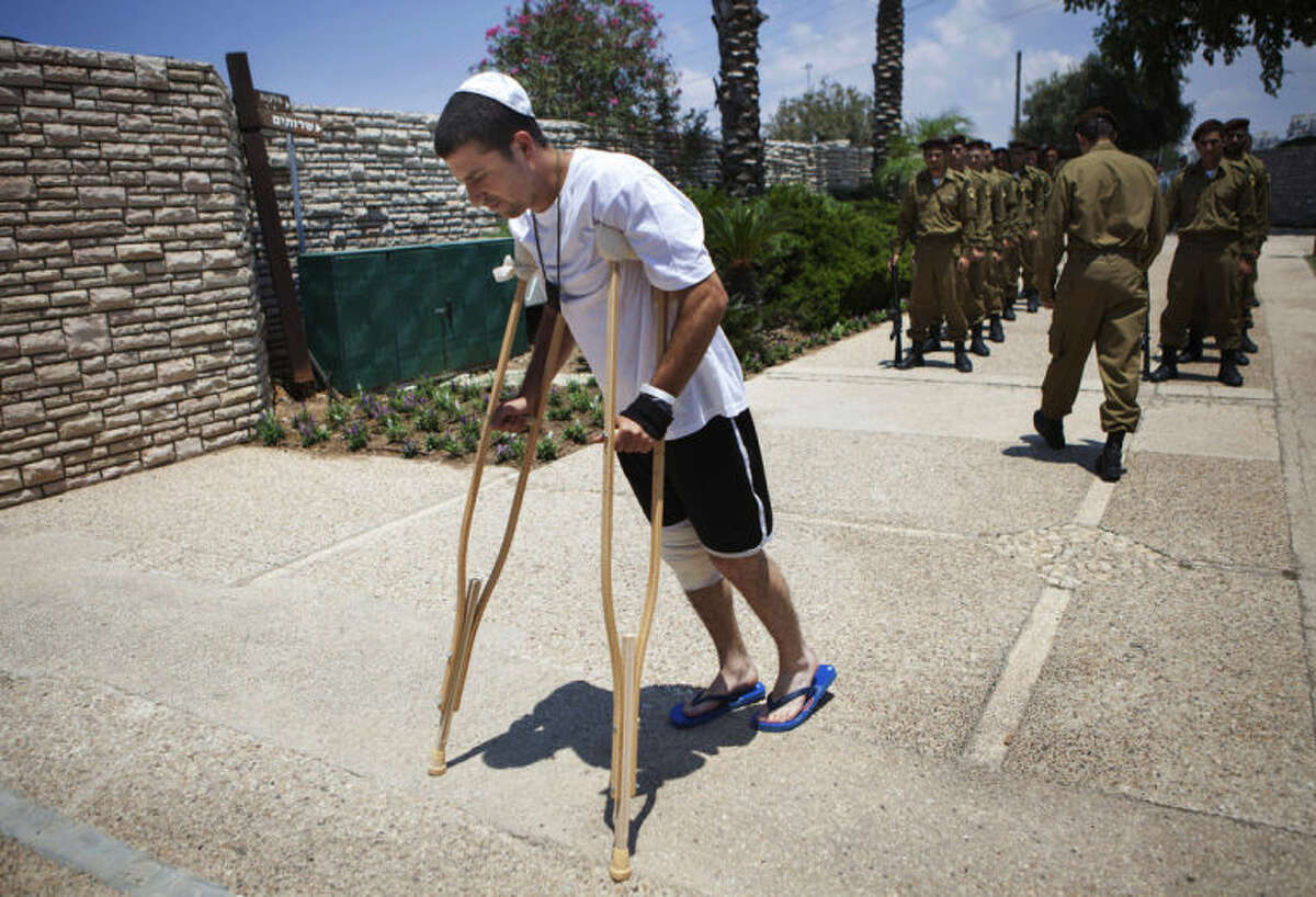 An Israeli wounded soldier arrives for the funeral of Maj. Tzafrir Bar-Or, 32, one of 13 solider's who were killed in several separate incidents in Shijaiya on Sunday, at the military cemetery in Holon, Monday, July 21, 2014. On Sunday, the first major ground battle in two weeks of Israel-Hamas fighting exacted a steep price, killing scores of Palestinians and more than a dozen Israeli soldiers and forcing thousands of terrified Palestinian civilians to flee their devastated Shijaiyah neighborhood, which Israel says is a major source for rocket fire against its civilians. The 13 Israeli soldiers were killed in Shijaiya, in gun battles and rocket attacks. In the deadliest, Gaza fighters detonated a bomb near an armored personnel carrier, killing seven soldiers inside, the army said. In another incident, three soldiers were killed when they became trapped in a burning building, it said. (AP Photo/Dan Balilty)