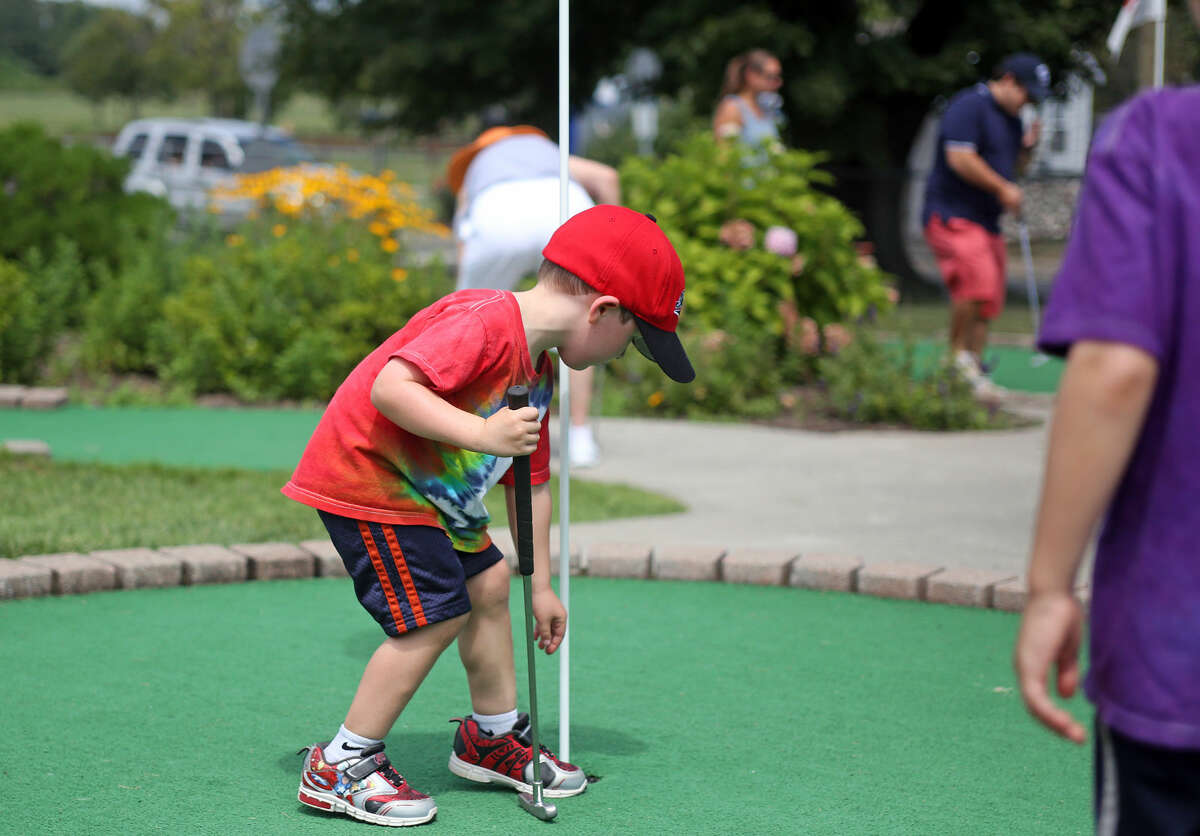 Zach Brill, 4, picks up his ball at Norwalk Cove Marina Mini Golf Sunday afternoon. Hour Photo / Danielle Calloway