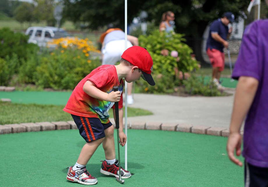 Zach Brill, 4, picks up his ball at Norwalk Cove Marina Mini Golf Sunday afternoon. Hour Photo / Danielle Calloway
