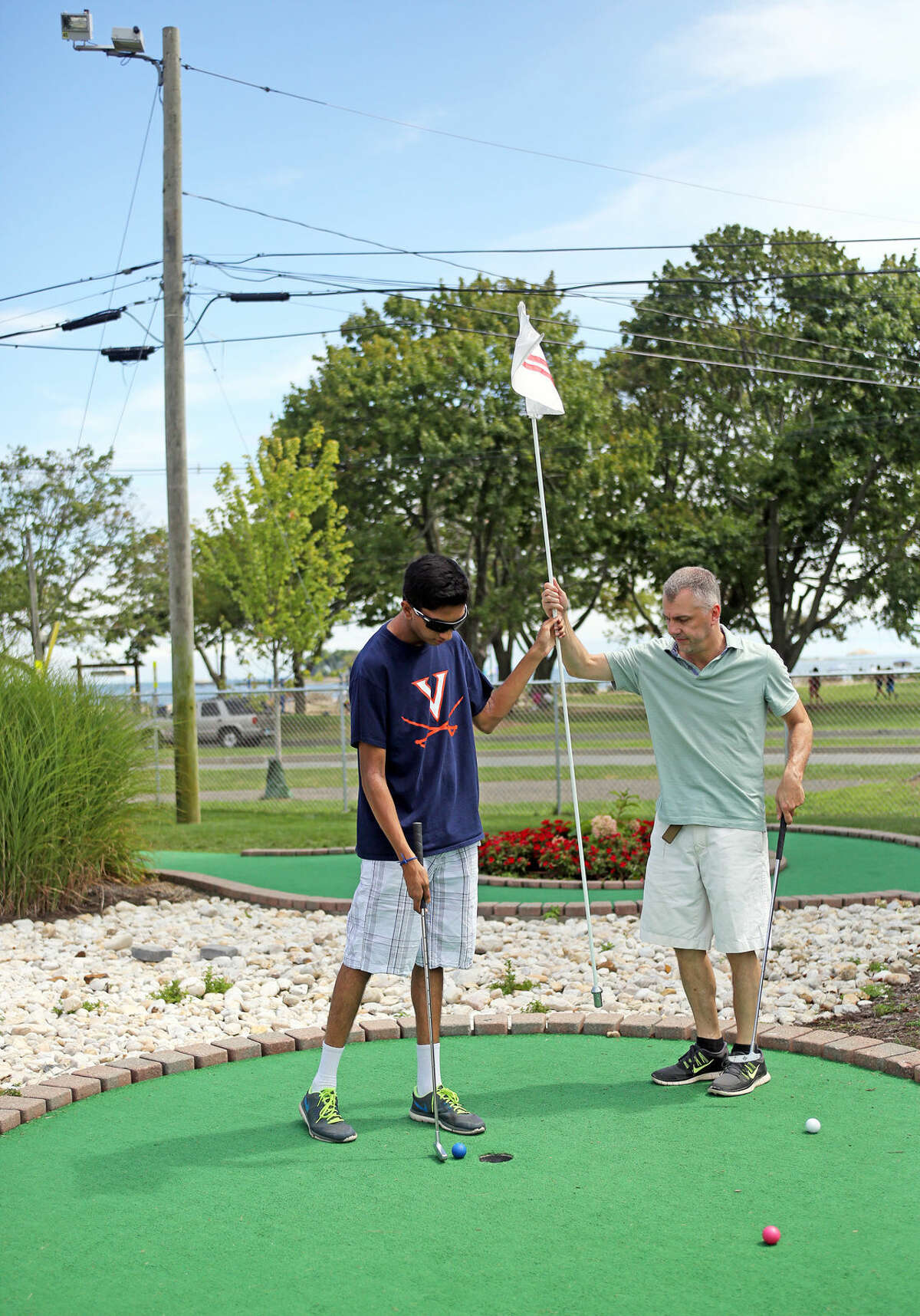 Steve Gatto plays a round with her Sanjeev Jariwala at Norwalk Cove Marina Mini Golf Sunday afternoon. Hour Photo / Danielle Calloway