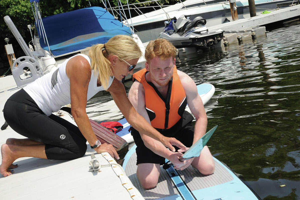 Hour Correspondent Justin McCabe learning to paddleboard on the Norwalk River from instructor Nancy Breakstone from the Norwalk Boat Club. Hour photo/Matthew Vinci