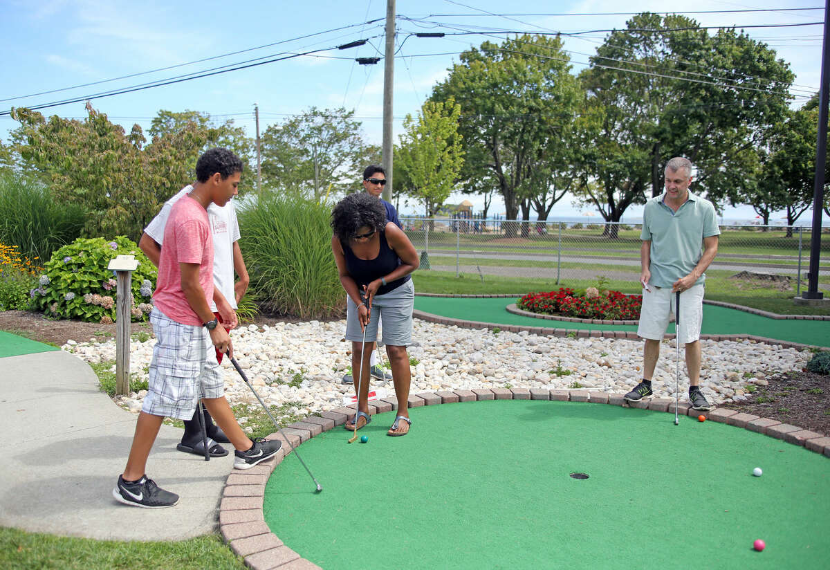 Carla Gatto plays a round with her family at Norwalk Cove Marina Mini Golf Sunday afternoon. Hour Photo / Danielle Calloway