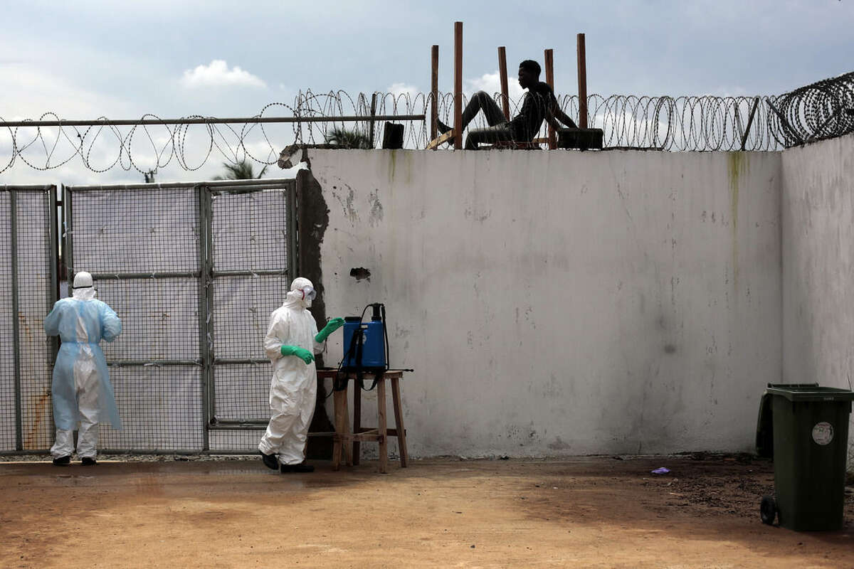 FILE - In this Friday, Sept. 26, 2014 file photo, health workers stand outside the Island Clinic Ebola isolation and treatment center in Monrovia, Liberia. Lingering health problems afflicting many of the roughly 13,000 Ebola survivors have galvanized global and local health officials seeking to determine how widespread the ailments are, and how to remedy them, with the World Health Organization calling it an emergency within an emergency. (AP Photo/Jerome Delay, File)