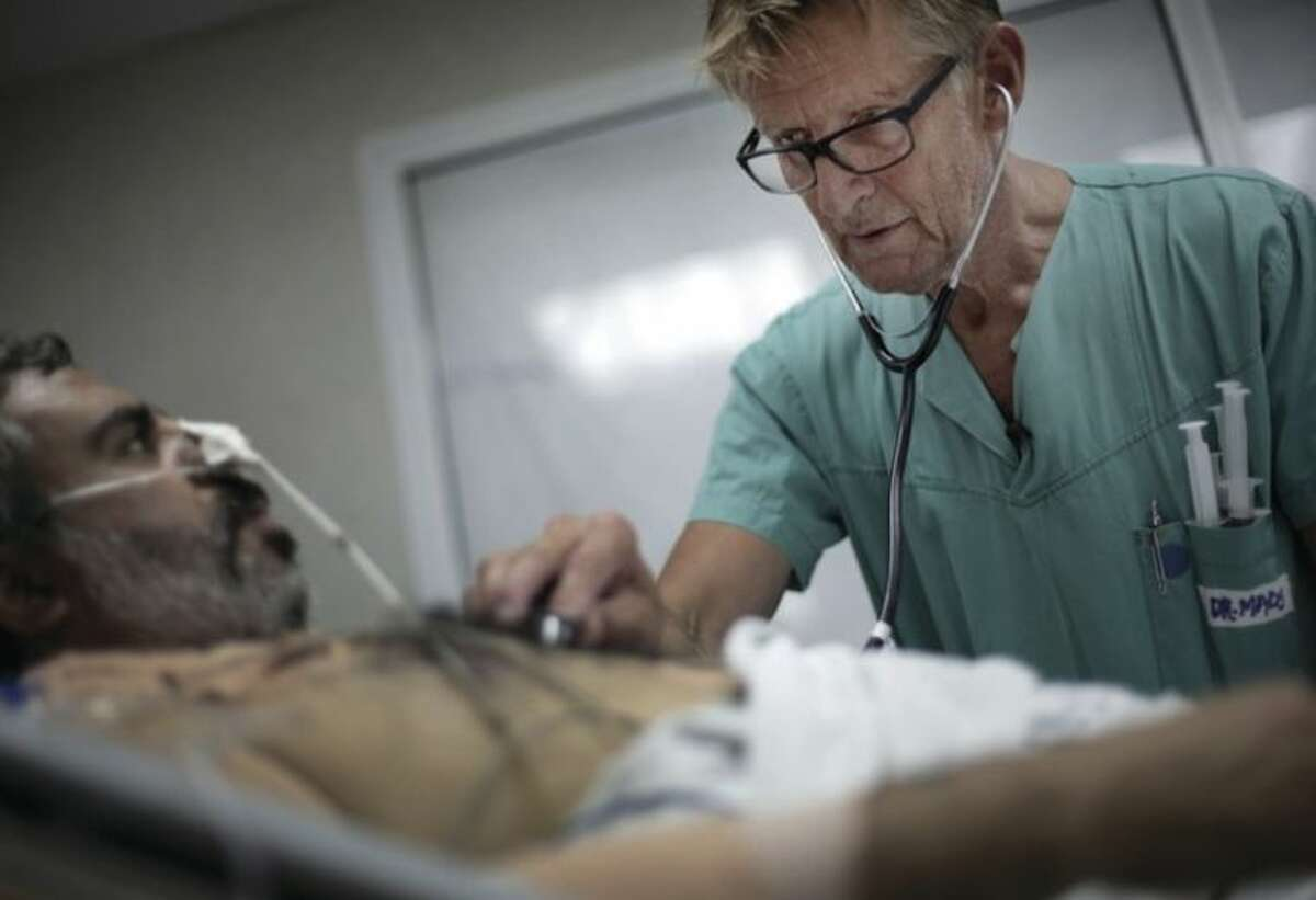 """In this Wednesday, July, 16, 2014, Mads Gilbert, Norwegian doctor who has volunteered at Shifa on and off for 17 years, treats a man at the emergency room of the Shifa hospital in Gaza City. Working at Shifa requires ingenuity. The power goes off repeatedly as aging hospital generators buckle under daily rolling blackouts Gaza residents have lived with for years. ?'If we are in the middle of an operation (and) lights go out, what do the Palestinians do? They pick up their phones, and they use the light from the screen to illuminate the operation field,?"""" said Gilbert. (AP Photo/Khalil Hamra)"""