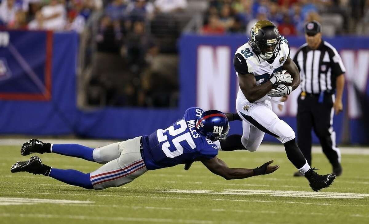 Jacksonville Jaguars' Bernard Pierce (30) breaks a tackle by New York Giants' Jeromy Miles (25) during the first half of a preseason NFL football game Saturday, Aug. 22, 2015, in East Rutherford, N.J. (AP Photo/Adam Hunger)