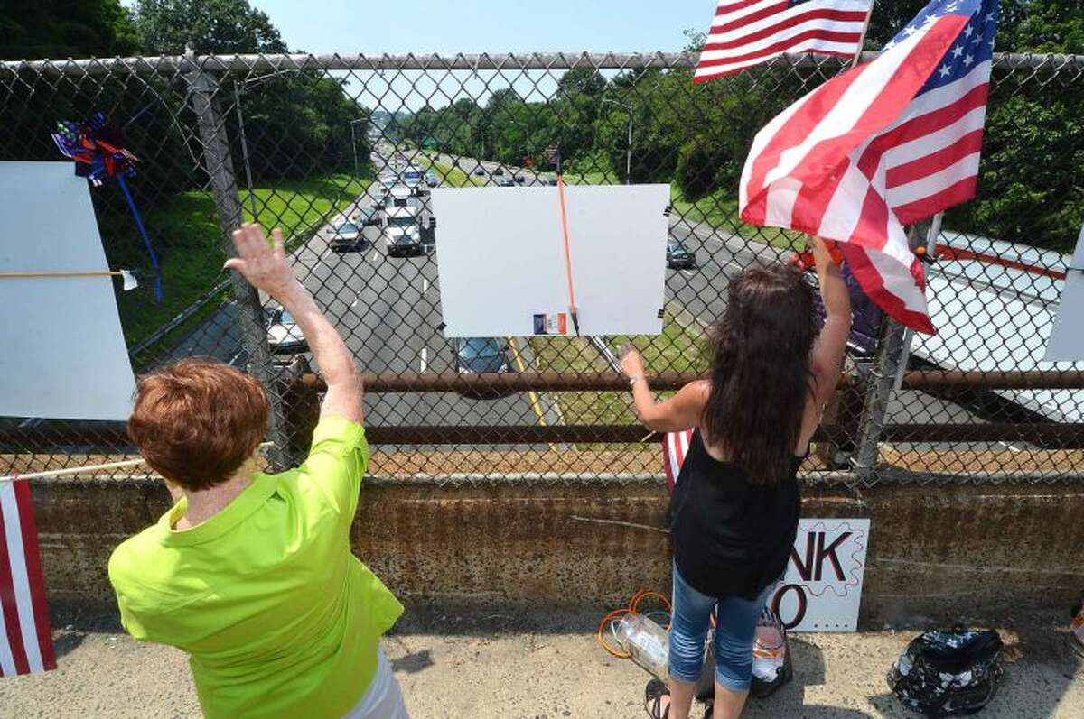 Hour Photo/Alex von Kleydorff On Strawberry Hill ave Friday, Nancy Krysiak and Brenda Gaffney get the attention of motorists on I95 Northbound as they honk their horns in support. The New England Overpasses for America group were protesting immigration amnesty for the recent wave of children crossing the border into the US
