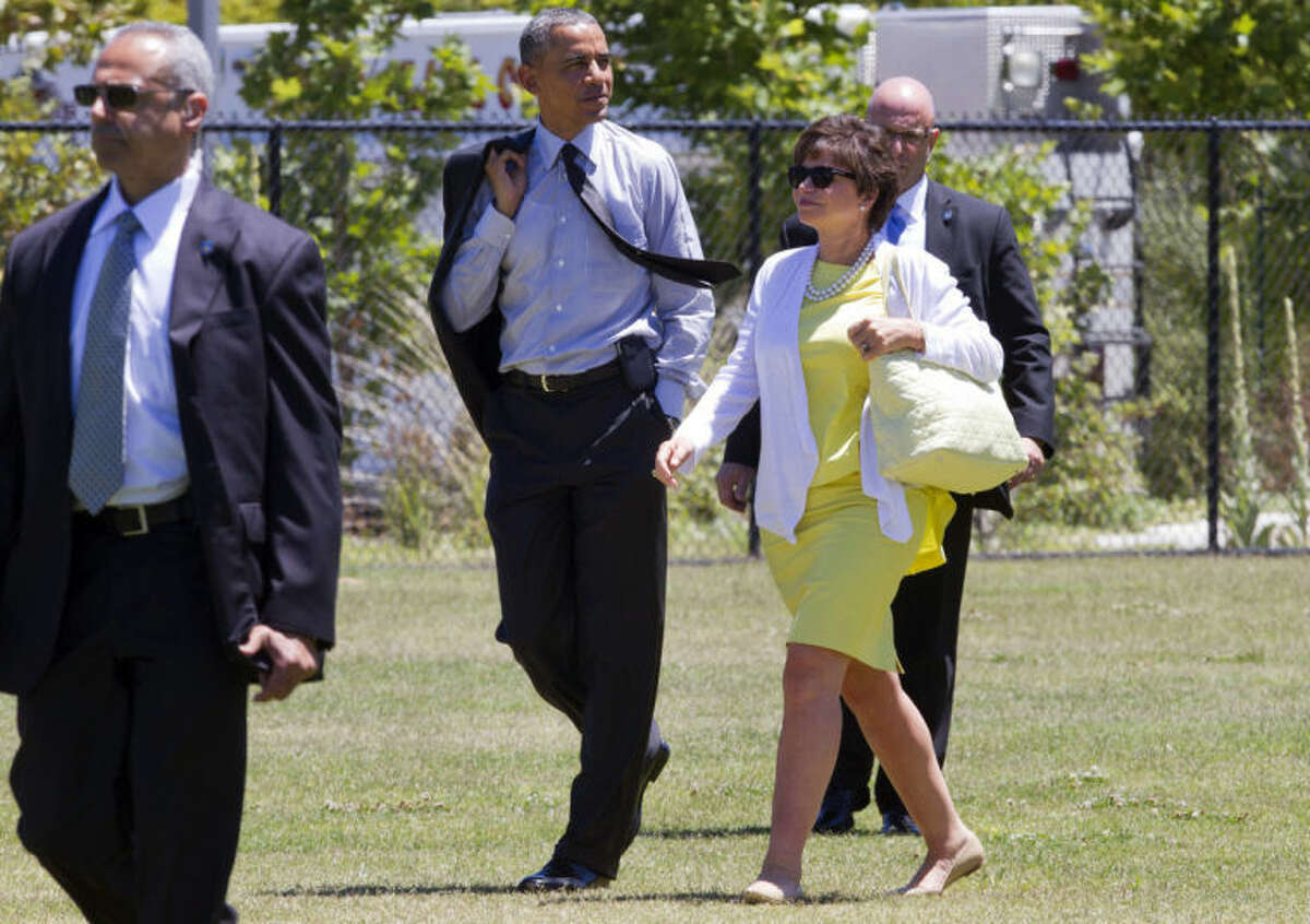 In this July 23, 2014, photo, President Barack Obama walks with senior adviser Valerie Jarrett as he leaves a fundraising event in Los Altos Hills, Calif. When Obama attended the fundraiser for the Democratic Congressional Campaign Committee, a party committee that must adhere to strict contribution limits, officials released the number of guests attending and how much they paid. For years Obama railed against the surge of unlimited spending flowing into American political campaigns, arguing that average voters were being shut out of a secretive system that lets special interests bankroll elections. Now as Obama enthusiastically raises money for Democratic super PACs, he?'s embracing some of the same secretive elements of that system, drawing charges of hypocrisy from good-governance advocates who say the public deserves to know what Obama?'s saying and whom he?'s saying it to when donors pay for a few minutes with the president.(AP Photo)