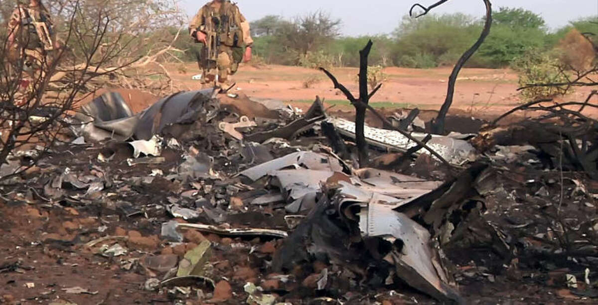 This photo provided Friday July 25, 2014 by the French army shows soldiers at the site of the plane crash in Mali. French soldiers secured a black box from the Air Algerie wreckage site in a desolate region of restive northern Mali on Friday, the French president said. Terrorism hasn't been ruled out as a cause, although officials say the most likely reason for the catastrophe that killed all onboard is bad weather. At least 116 people were killed in Thursday's disaster, nearly half of whom were French. (AP Photo/ECPAD)