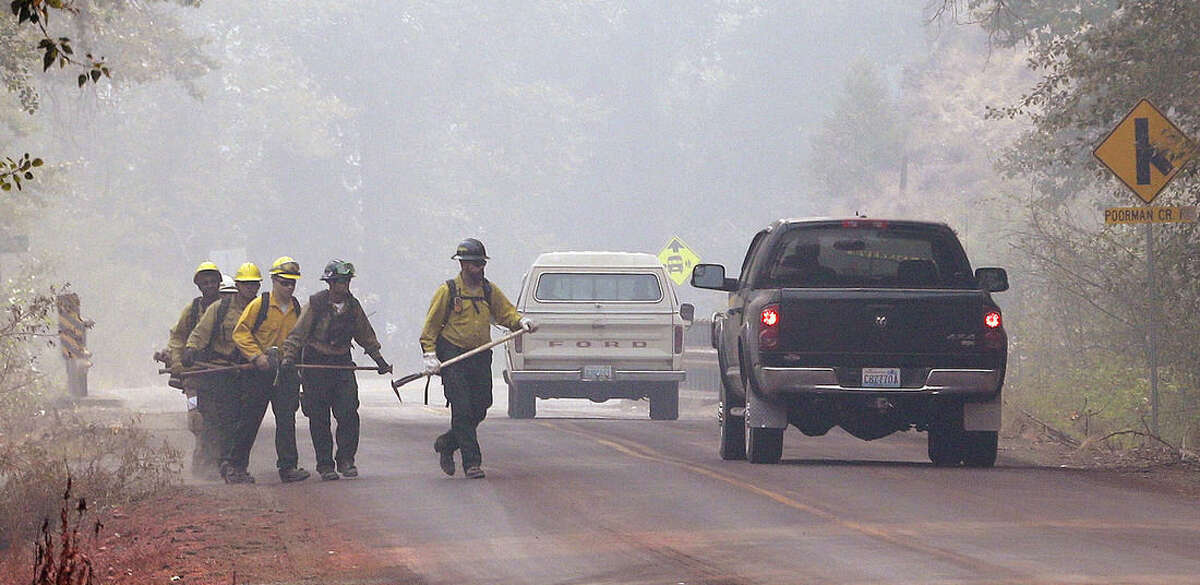 Firefighters walk through heavy smoke Sunday, Aug. 23, 2015, in Twisp, Wash. Firefighters across the West saw little relief over the weekend as wildfires raged in the drought-stricken region, but for those in Washington, other states will soon provide additional resources. (AP Photo/Elaine Thompson)