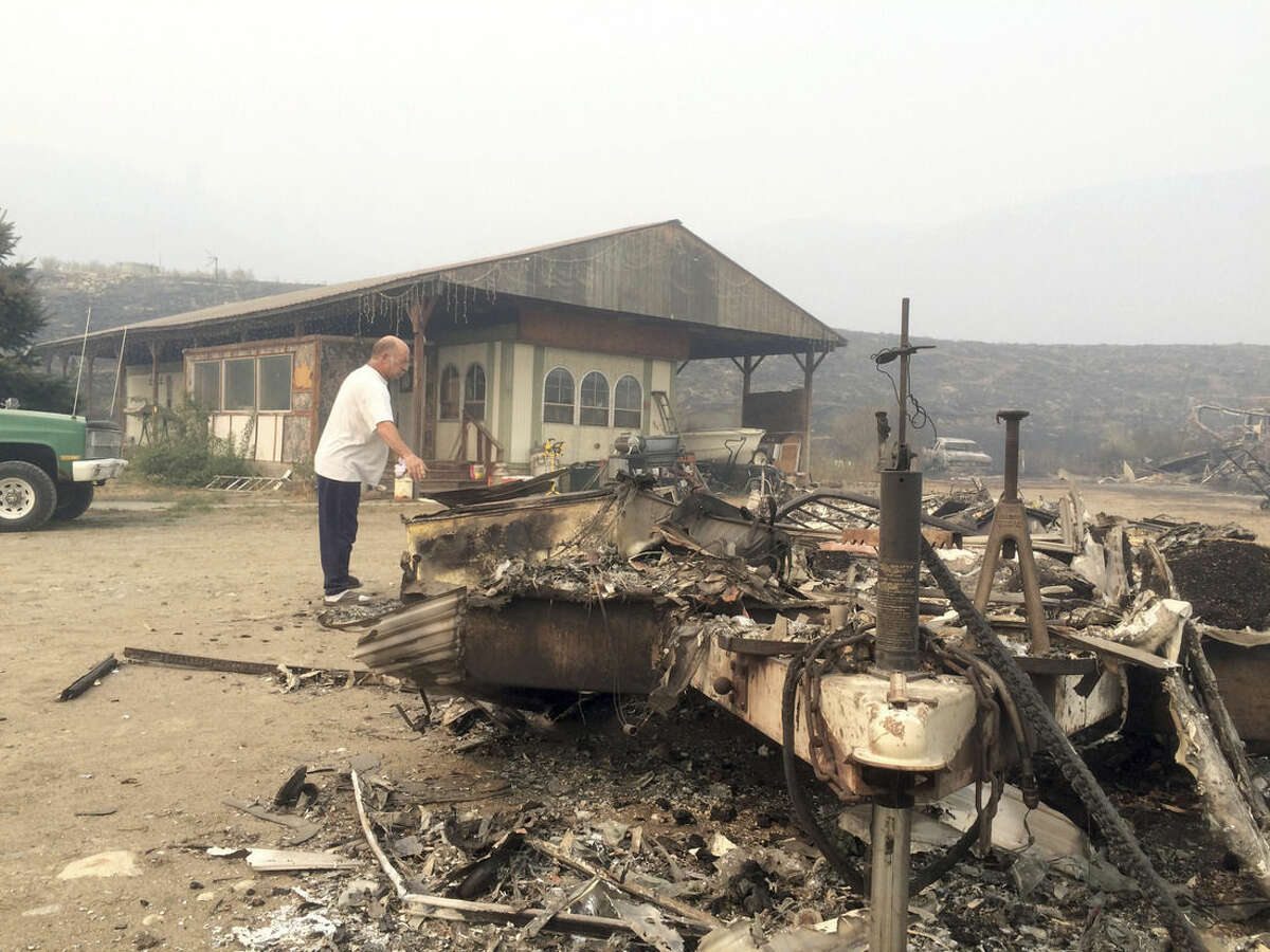 Steve Surgeon surveys the ruins after he lost everything he owned except his home in a wildfire on the outskirts of Okanogan, Wash., Sunday, Aug. 23, 2015. He said he stayed as the fire raced over a ridge and barreled down toward his home, flames lapping just feet from his back porch. Surgeon estimates he lost more than $100,000 worth of property, including his shop, his motorcycle, several cars, a travel trailer, and all of his tools.(AP Photo/Brian Skoloff)