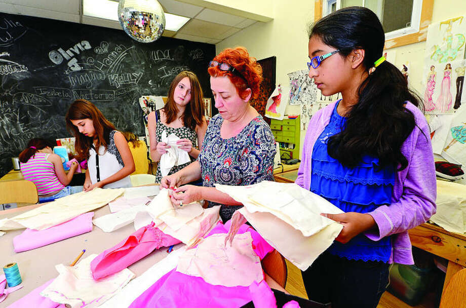 Hour photo / Erik Trautmann New England Fashion and Design Association president Irina Simeonova, center, helps her summer campers including Katie Rowe and Sofia Nazer Wednesday at their facility at the South Norwalk train station.