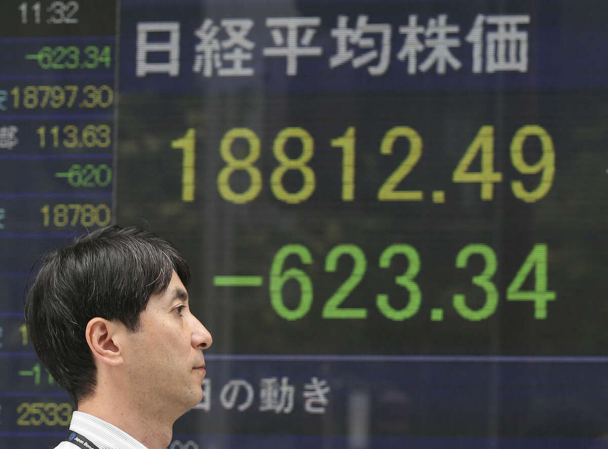 A man walks by an electronic stock board of a securities firm in Tokyo, Monday, Aug. 24, 2015. Stocks fell in early trading Monday in Asia as investors shaken by the sell-off last week on Wall Street unloaded shares in many sectors. (AP Photo/Koji Sasahara)