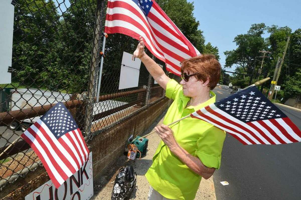Hour Photo/Alex von Kleydorff On Strawberry Hill ave Friday, Nancy Krysiak waves a flag as motorists on I95 Northbound honk their horns in support. The New England Overpasses for America group were protesting immigration amnesty for the recent wave of children crossing the border into the US