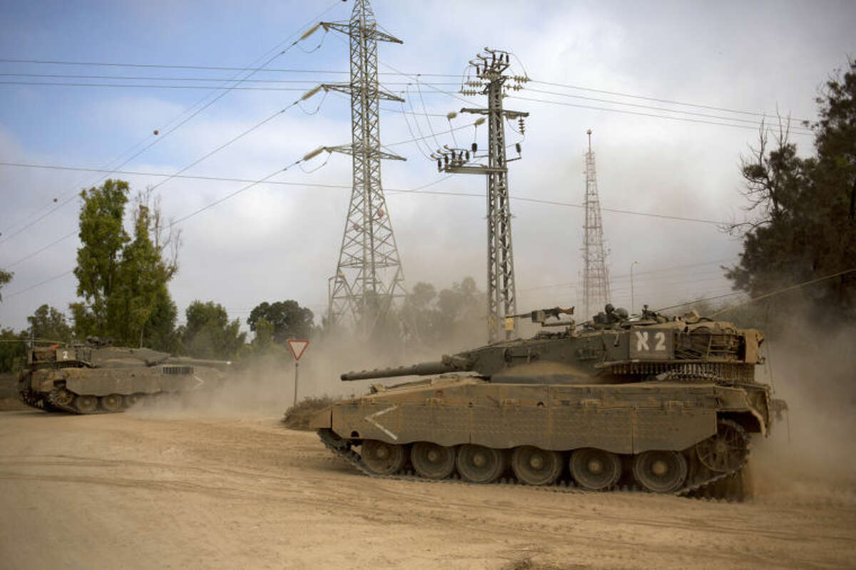 Israeli tanks move near the Israel and Gaza border Thursday, July 24, 2014. Israeli tanks and warplanes bombarded the Gaza Strip on Thursday, as Hamas militants stuck to their demand for the lifting of an Israeli and Egyptian blockade in the face of U.S. efforts to reach a cease-fire.(AP Photo/Dusan Vranic)