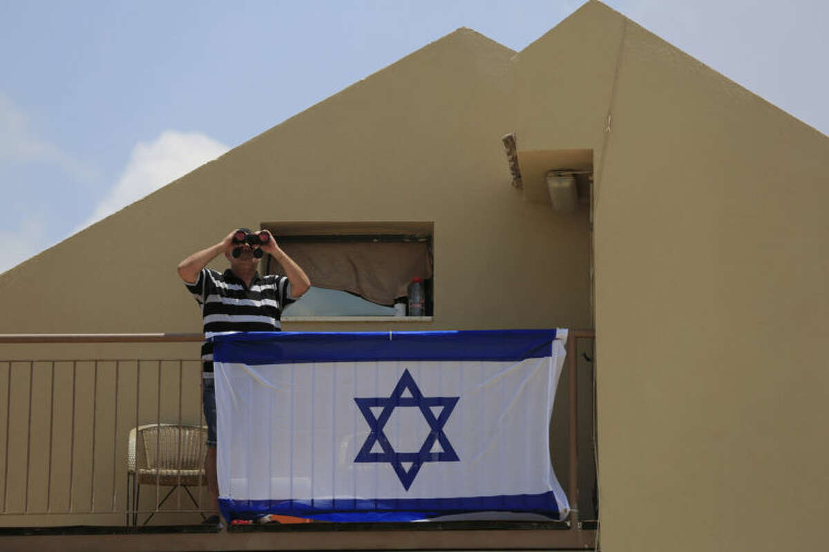 FILE - In this Monday, July 21, 2014 file photo, a man uses binoculars to look at the Gaza Strip from his balcony in the town of Sderot, Israel after a group of Hamas militants was detected infiltrating into Israel. With deadly fighting raging next door in the Gaza Strip, southern Israeli towns along the border have turned into mini army bases as most residents have fled. (AP Photo/Tsafrir Abayov, File)