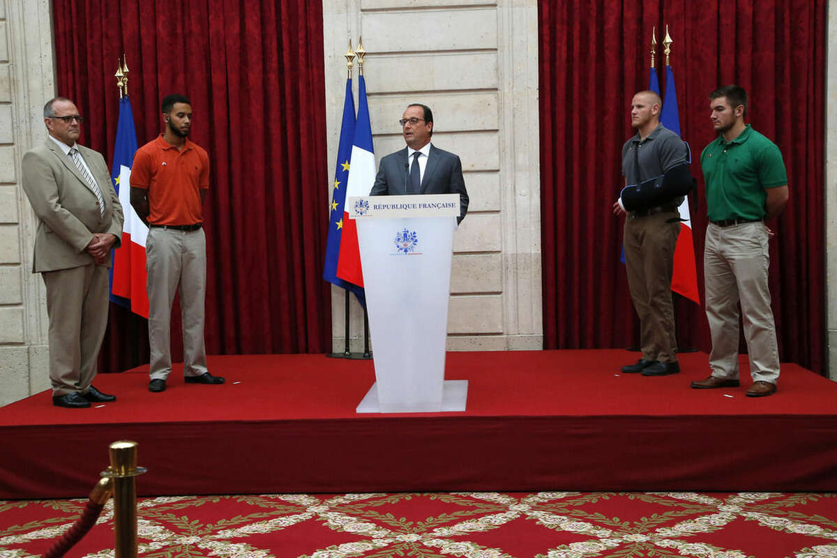From the left, British businessman Chris Norman, Anthony Sadler, a senior at Sacramento University in California , U.S. Airman Spencer Stone, second right, and U.S. National Guardsman from Roseburg, Oregon, Alek Skarlatos, right, listen to French President Francois Hollande, center, at the Elysee Palace, Monday Aug.24, 2015 in Paris, France. Three Americans and a British man who took down a heavily armed man on a passenger train speeding through Belgium have received France's top honor.(AP Photo/Michel Euler, Pool)