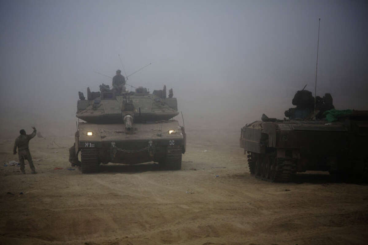 An Israeli tank moves through the morning mist near the Israel and Gaza border Thursday, July 24, 2014. Israeli tanks and warplanes bombarded the Gaza Strip on Thursday, as Hamas militants stuck to their demand for the lifting of an Israeli and Egyptian blockade in the face of U.S. efforts to reach a cease-fire. (AP Photo/Dusan Vranic)