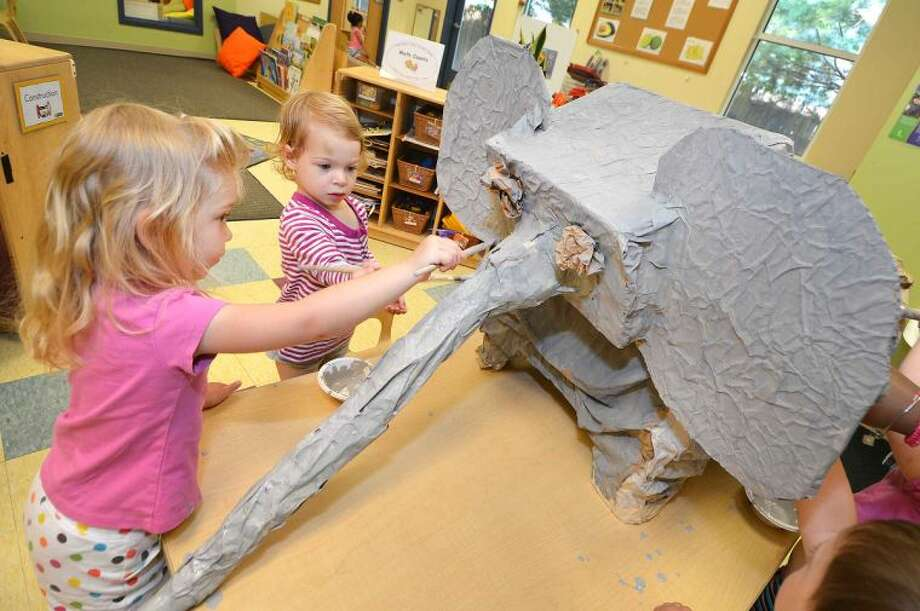 Carina Berry and Freya Cameron, both 3 years old, help classmates paint an elephant gray while making mock zoo animals out of recyclable materials for the Mock Zoo on Friday at Bright Horizons in Wilton.