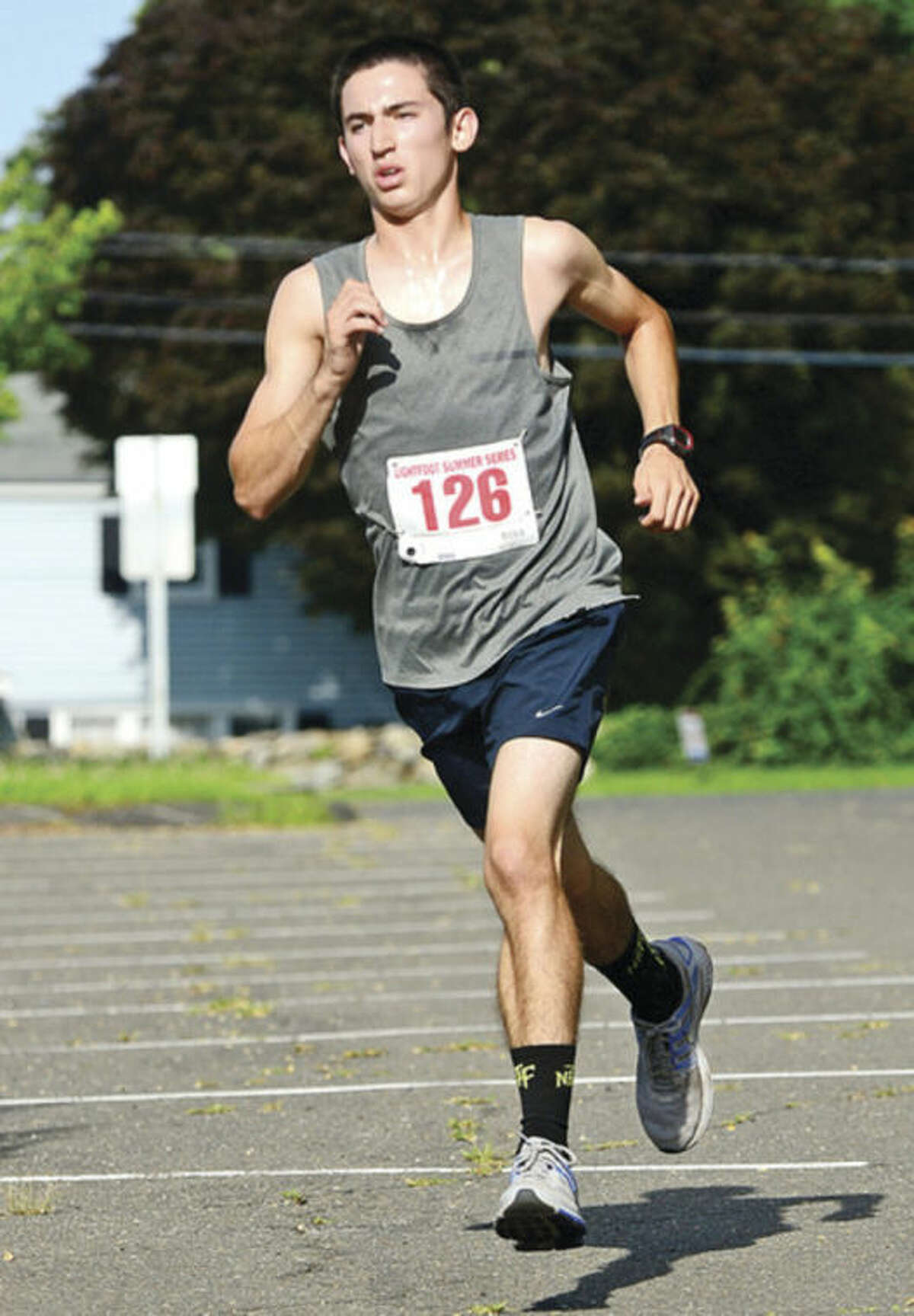 Hour photo/Erik Trautmann Eric van der Els races toward the finish line to win the Lightfoot Road Runners Series 7-mile road race at Brien McMahon High School on Saturday in Norwalk.