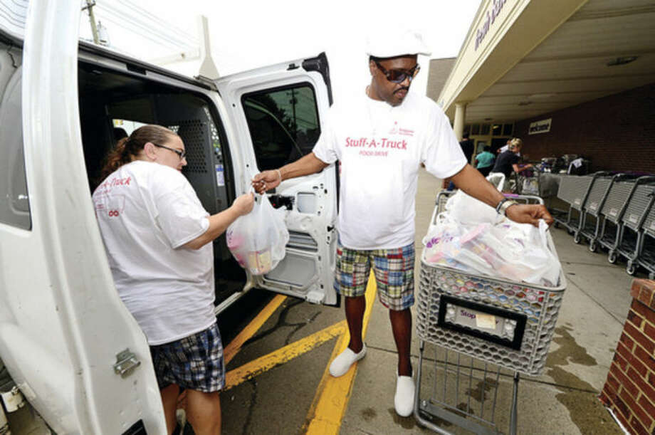 Bridgeport Rescue Mission's Melvin Klein loads donated groceries at Stop & Shop on CT Ave for their third annual Stuff-A-Truck food drive to feed hungry families.