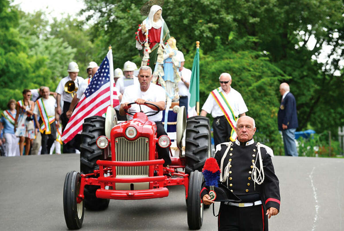 Hour photo / Erik Trautmann Members of St. Ann Club parade to and from St. Thomas Church as part of the annual St. Ann Feast on Hendricks Ave this weekend.
