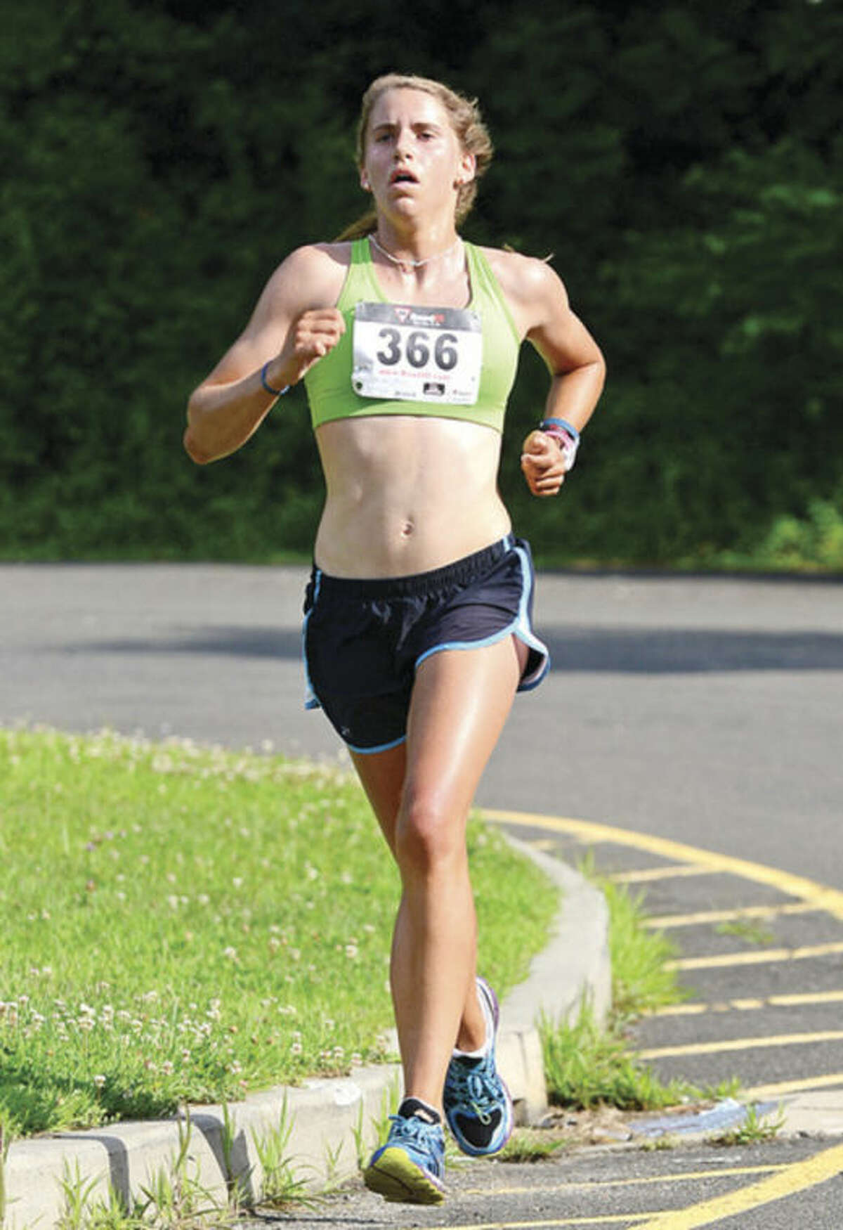 Hour photo / Erik Trautmann Anne Johnston finishes first for the women in the Lightfoot Road Runners road race, a 7-miler at Brien McMahon High School Saturday.