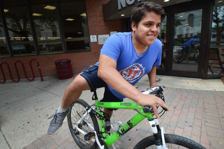 Hour Photo/Alex von Kleydorff Brian Green takes off from The library on his bike, excited about the possibilty of bike lanes on Belden Ave