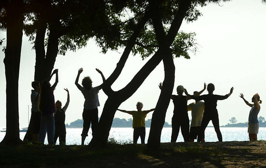 Hour photo / Erik Trautmann Area residents practice Tai Chi at Shady Beach in Norwalk Wednesday morning.