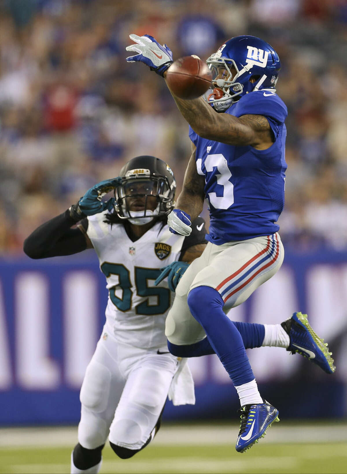 New York Giants wide receiver Odell Beckham (13) leaps for a ball thrown by quarterback Eli Manning as Jacksonville Jaguars' Demetrius McCray (35) watches during the first half of a preseason NFL football game Saturday, Aug. 22, 2015, in East Rutherford, N.J. The pass was incomplete. (AP Photo/Adam Hunger)