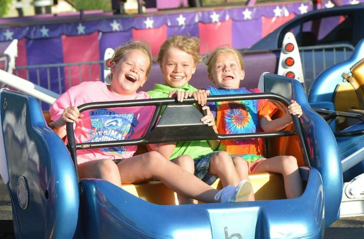 Hour Photo/Alex von Kleydorff Maggie, AJ, and Kate Fedor squeeze a ride on the Sizzler during opening night at the St. Ann Club Feast