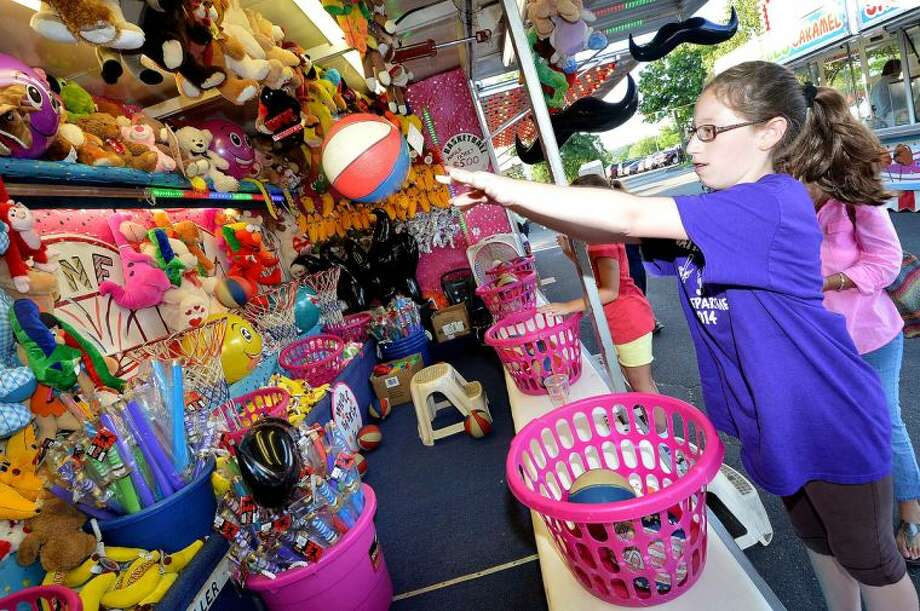 Hour Photo/Alex von Kleydorff Sara Guaglione makes a shot to win a prize as The St. Ann Club Feast gets underway this weekend and the club celebrates its Centennial with rides, food and fun for all
