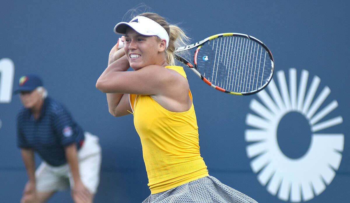 Hour photo/John Nash - Caroline Wozniacki of Denmark watches a backhand return sail over the net during her second round match against Roberta Vinci of Italy at the Connecticut Open tennis tournament in New Haven on Wednesday.