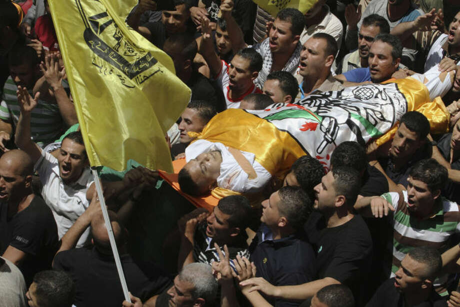 Palestinians carry the body of Eid Fadhelat, 32, who was injured during clashes with Israeli soldiers Friday, during his funeral at Al-Arrub refugee camp near Hebron city in the West Bank on Saturday, July 26, 2014. Eid Fadhelat was shot during clashes that started late Friday with Israeli troops at the refugee camp and died later. In the West Bank, which had been relatively calm for years, protests raged Friday against Israel's Gaza operation and the rising casualty toll there. (AP Photo/Nasser Shiyoukhi)