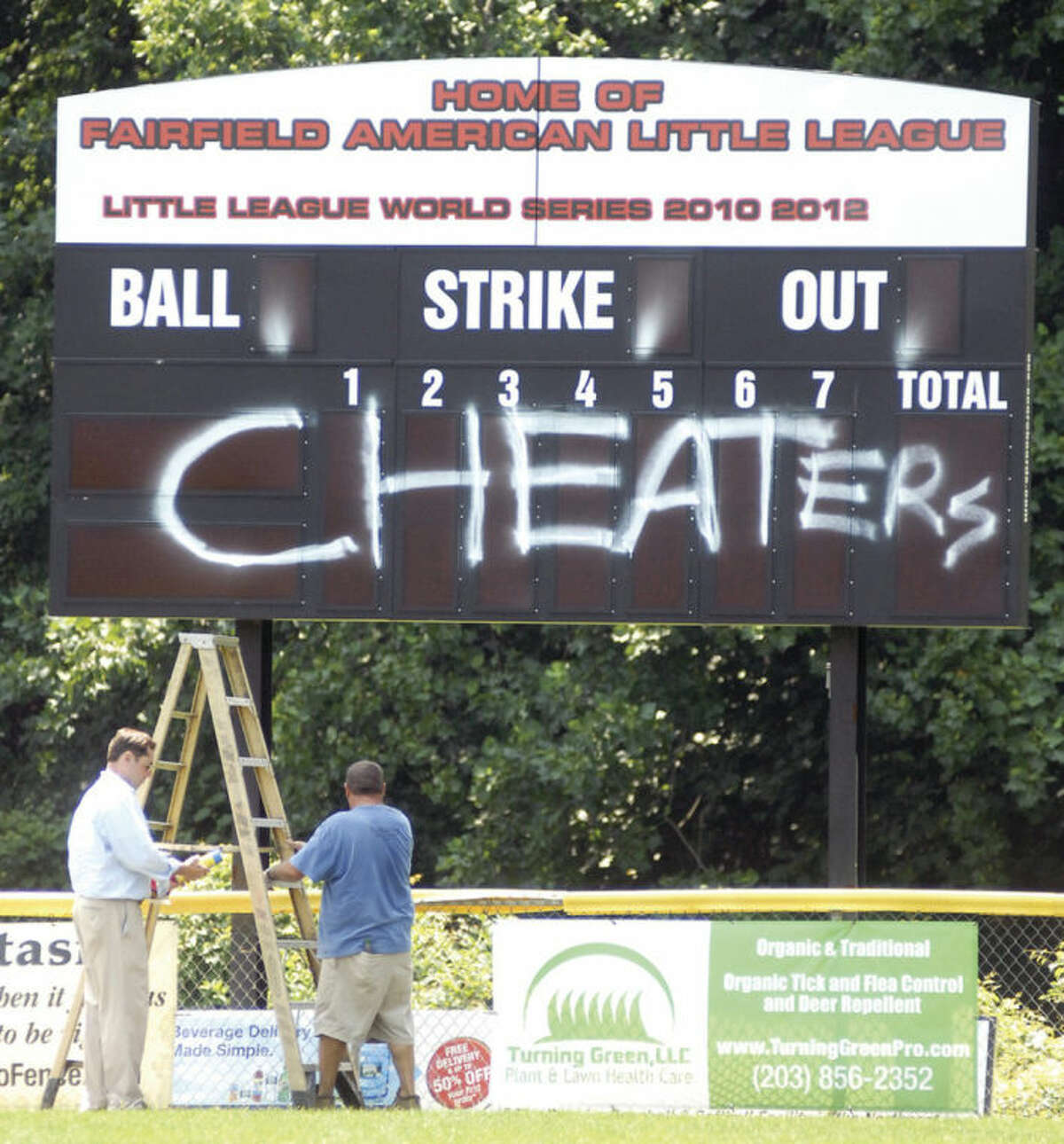 Hour photo/John Nash Members of the Fairfield American Little League coaching staff survey the damage done by vandals in the wake of the team's Section 1/Division 1 championship win over Norwalk.