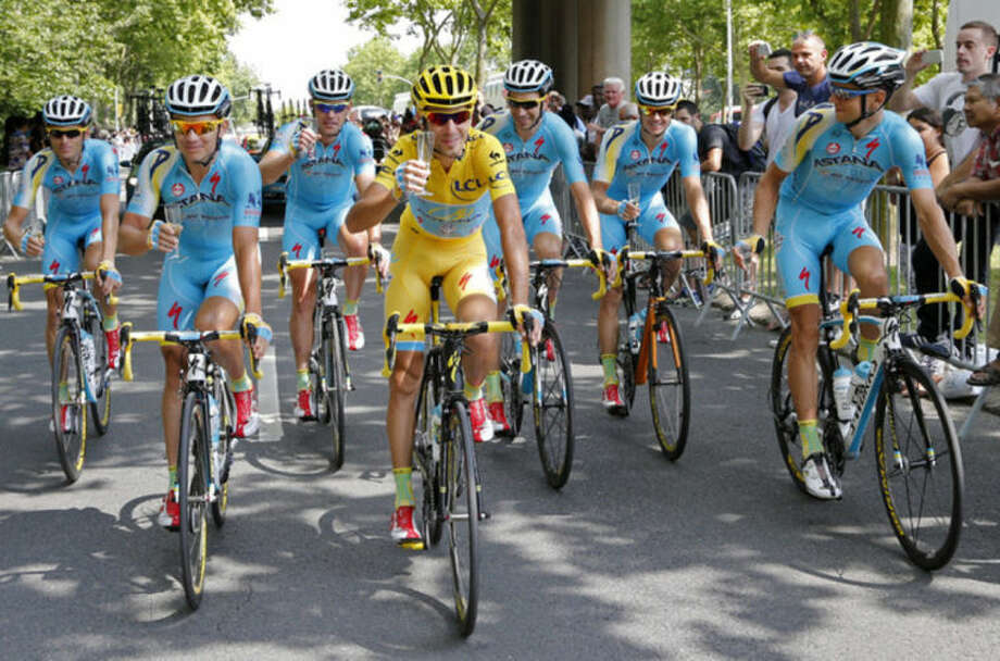 Team Astana with Italy's Vincenzo Nibali, wearing the overall leader's yellow jersey, celebrates with a glass of champagne during the twenty-first and last stage of the Tour de France cycling race over 137.5 kilometers (85.4 miles) with start in Evry and finish in Paris, France, Sunday, July 27, 2014. (AP Photo/Jean-Paul Pelissier, Pool)