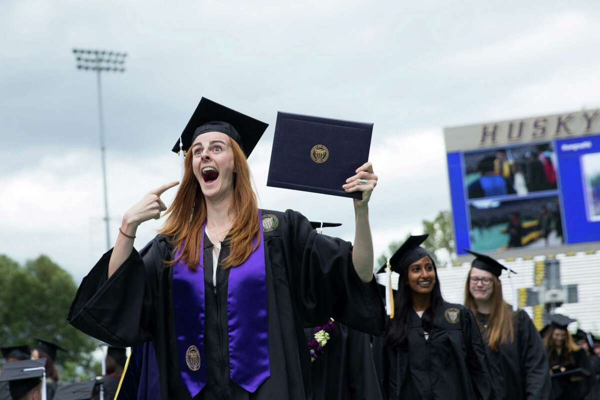 A graduate gestures toward the crowd after receiving her diploma during the University of Washington's 141st annual commencement exercises at Husky Stadium in Seattle, Saturday, June 11, 2016.