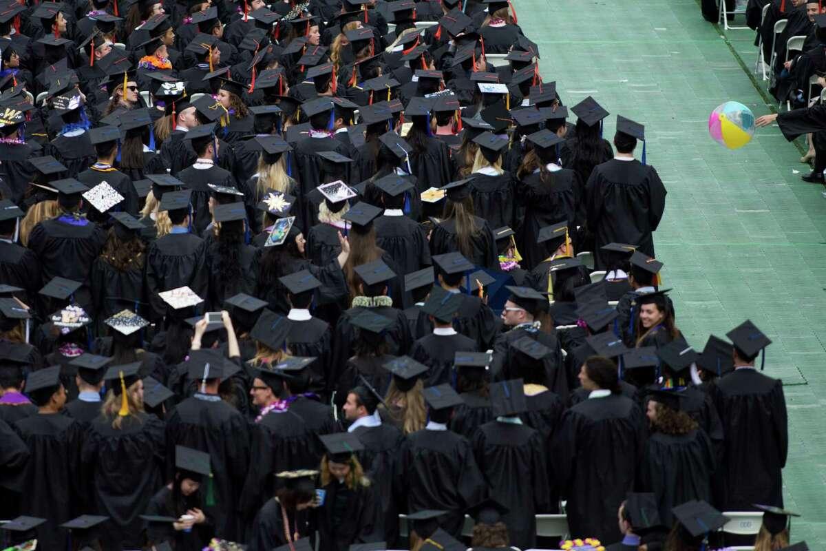 A graduate knocks a beach ball in the aisle.