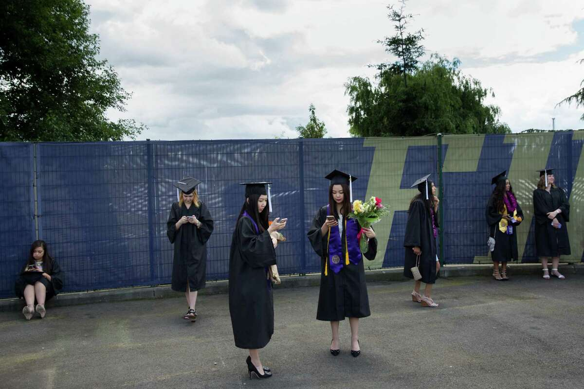 Graduates use their smartphones before the ceremony.