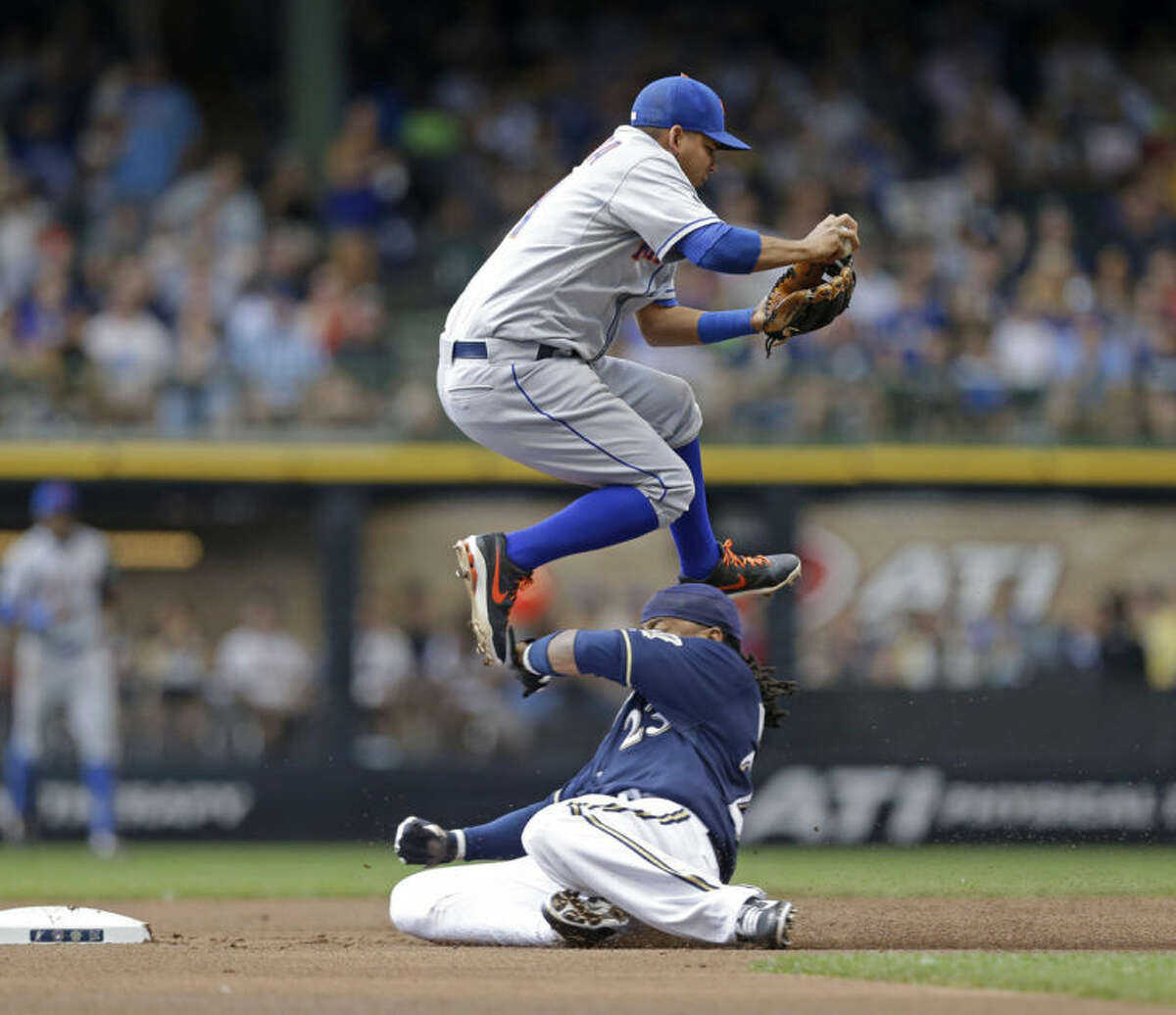 New York Mets' Ruben Tejada, top, forces out Milwaukee Brewers' Rickie Weeks on a ball hit by Brewers' Ryan Braun during the first inning of a baseball game Sunday, July 27, 2014, in Milwaukee. (AP Photo/Jeffrey Phelps)