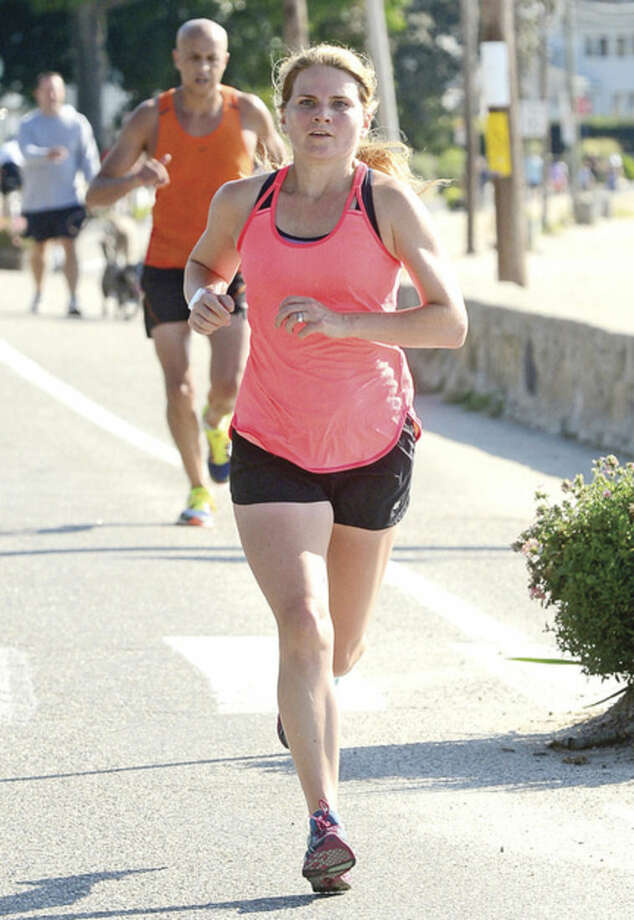 Hour photo / Erik Trautmann Kate Pfeffer is the first woman finisher during the Westport Road Runners Summer Series 9.3 mile race at Compo Beach Saturday.