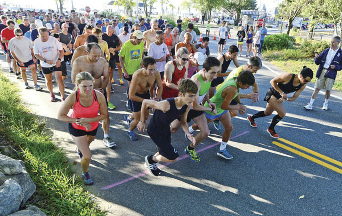 Hour photo / Erik Trautmann Runners take off at the starting line on Saturday at the Westport Road Runners Summer Series 9.3 mile race at Compo Beach.