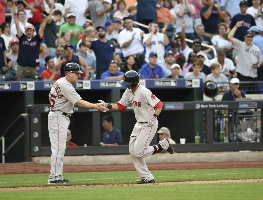 Boston Red Sox fans cheer as Red Sox center fielder Mookie Betts (50) shakes hands with third base coach Brian Butterfield (55) as he rounds third base after hitting a solo home run off of New York Mets relief pitcher Hansel Robles in the seventh inning of a baseball game at Citi Field on Saturday, Aug. 29, 2015, in New York. (AP Photo/Kathy Kmonicek)